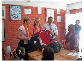 Dr. Amanda Marshall and Dr. Robyn Hakanson present Jerseys from Jersey soccer uniforms to young girls who are part of the Little Sisters program in Kathmandu, Nepal during WOGO's inaugural medical mission.